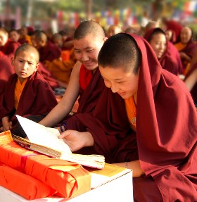 young monks reading in the new dharma books provided during the Worl Peace Ceremony