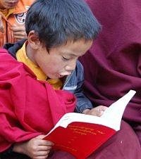 Young novice reads his new Tibetan book, donated through Adopt a Dharma Book, photo by Ed Palmer.